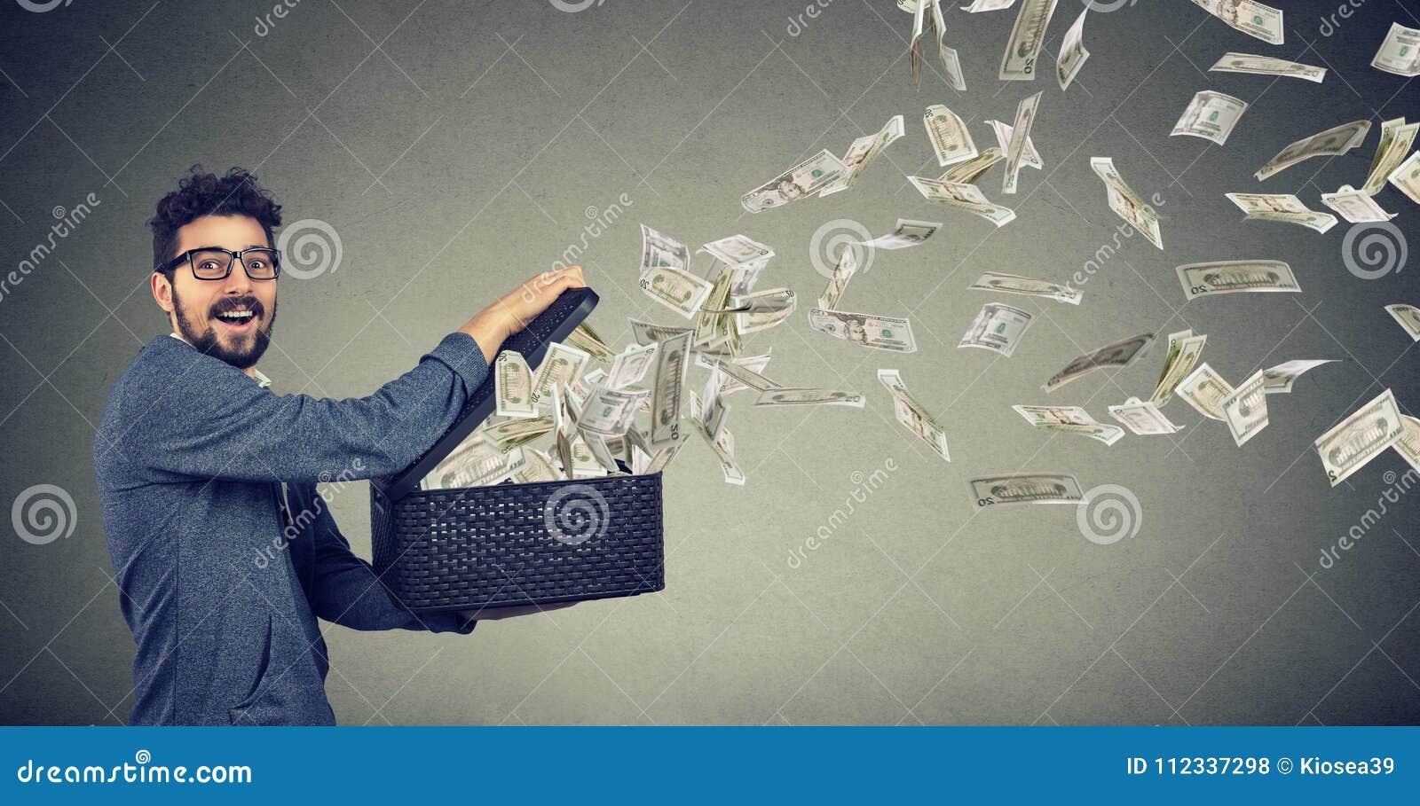 Biznesowy mężczyzna otwiera pudełko pozwala dolarowych banknoty latać daleko od