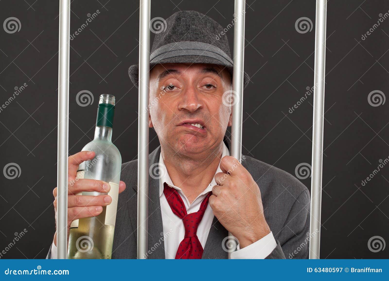 Biznesowy mężczyzna pijący w więzieniu