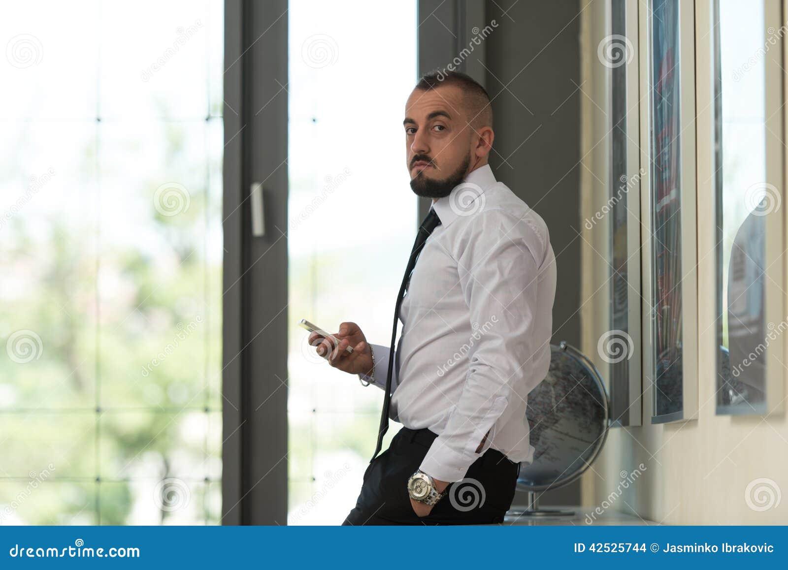 Biznesowy mężczyzna Texting Na telefonie komórkowym W Nowożytnym biurze