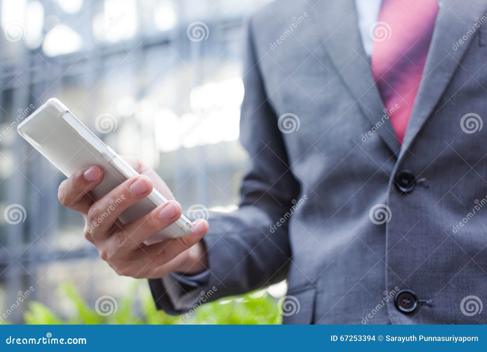 Biznesowy mężczyzna używa x28 & telefon komórkowego; ostrość na cellphone& x29;