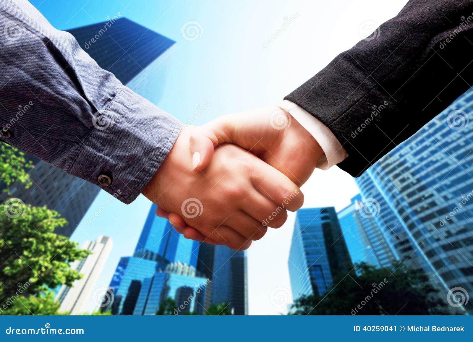 Biznesowy uścisk dłoni, drapacza chmur tło. Transakcja, sukces, współpraca