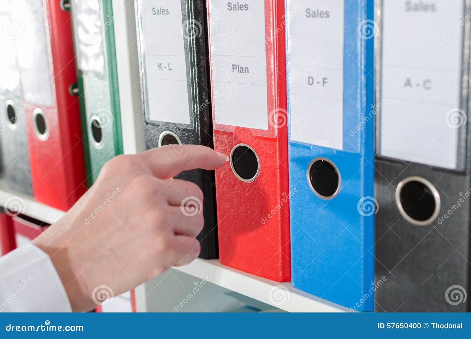 Bizneswoman bierze segregatoru od półki
