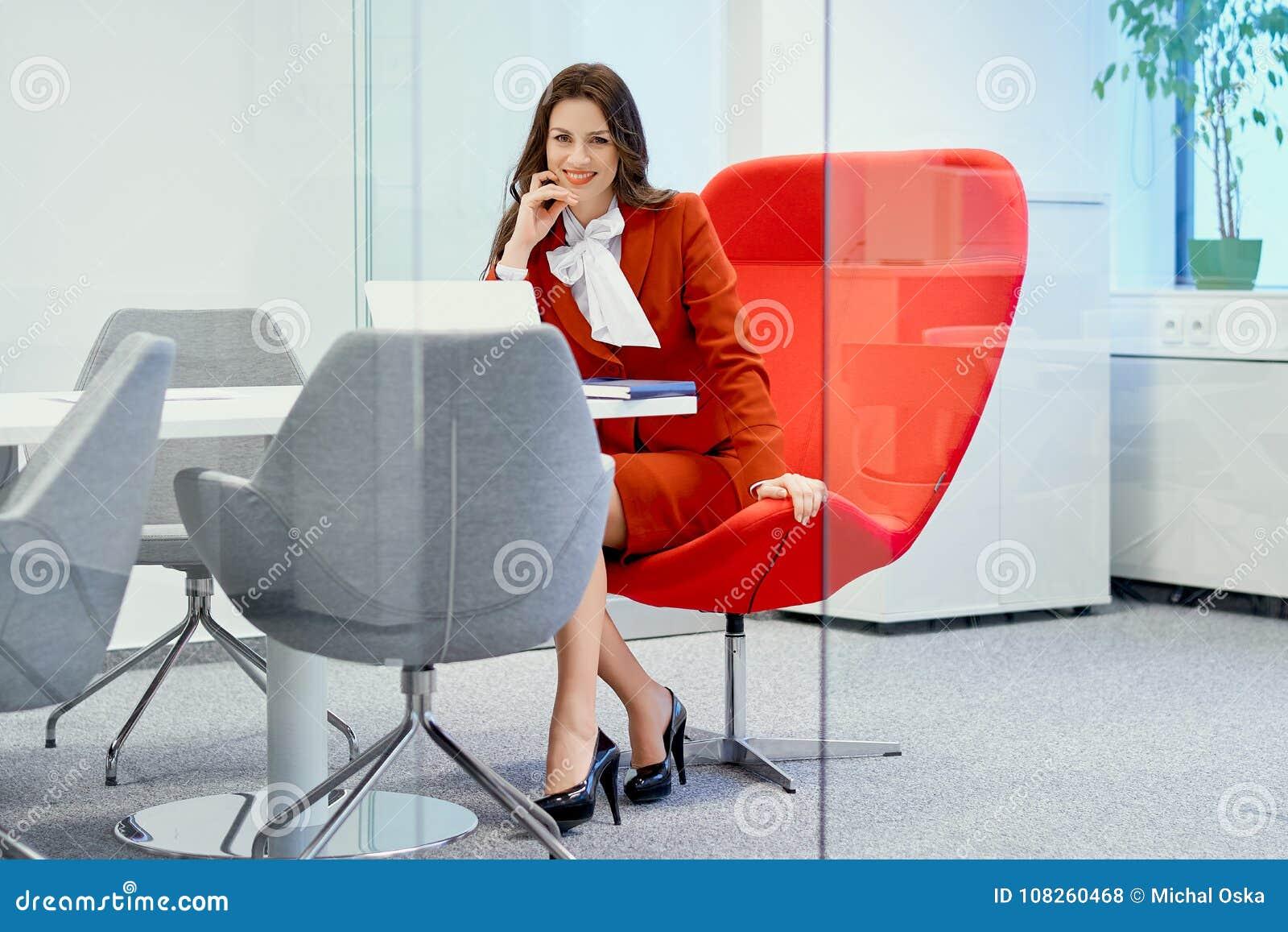 Bizneswoman ono uśmiecha się i siedzi na czerwonym krześle w szklanym biurze