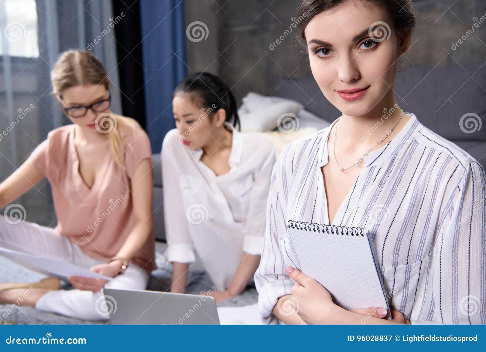 Bizneswoman patrzeje kamerę z notatnikiem w rękach