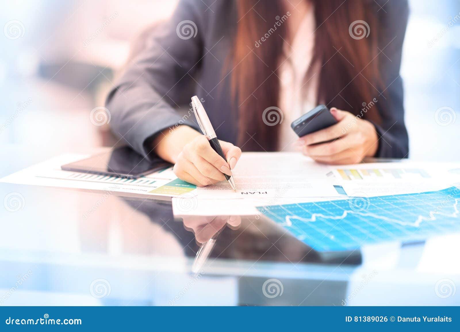 Bizneswoman pisze na dokumencie przy jej biurem