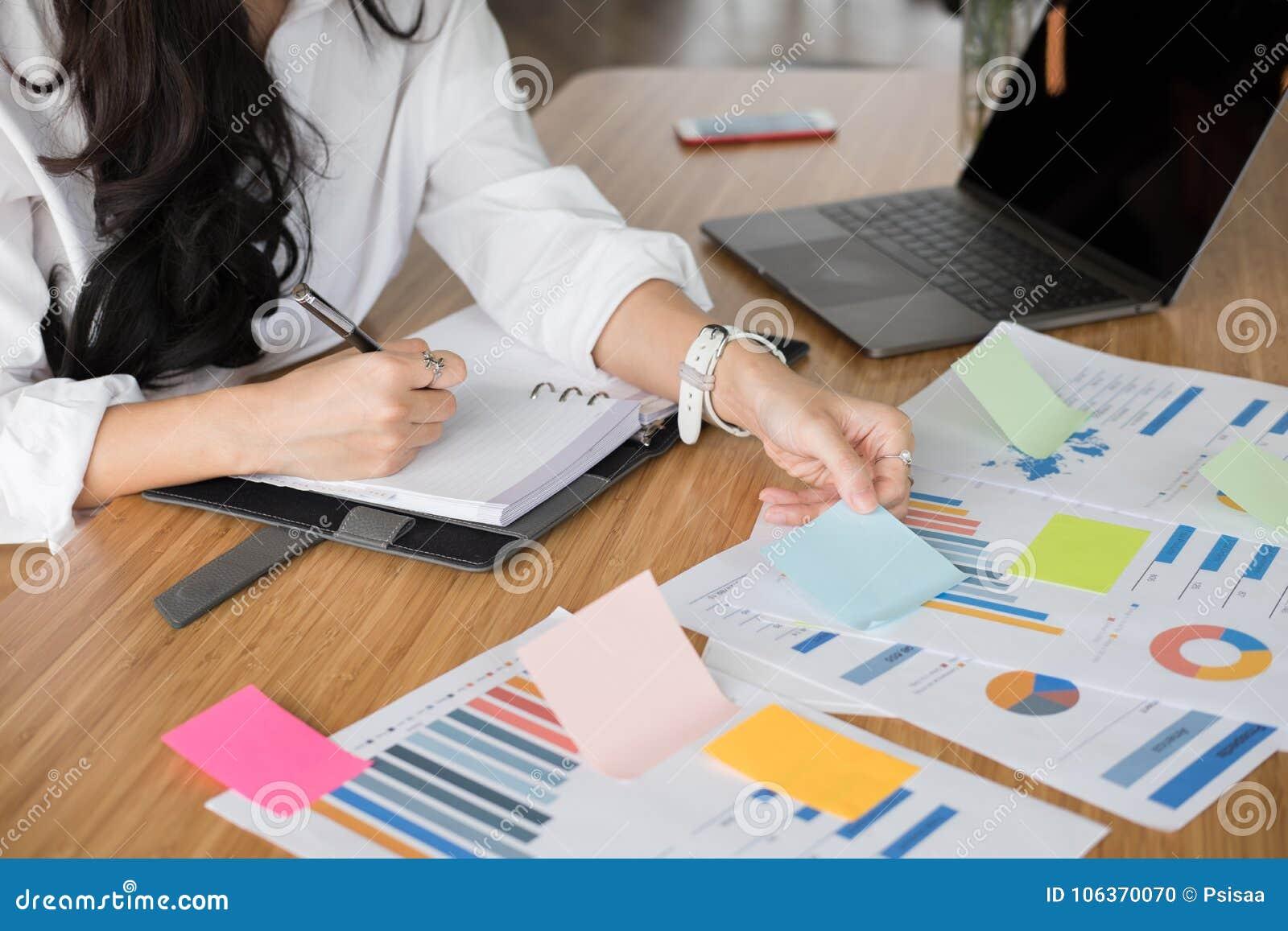 Bizneswoman pisze notatce na notatniku przy miejscem pracy początkowa kobieta