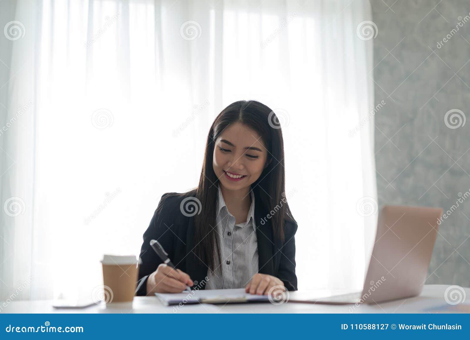 Bizneswoman podpisuje kontraktacyjnego papier w jej workstatio przy pracą
