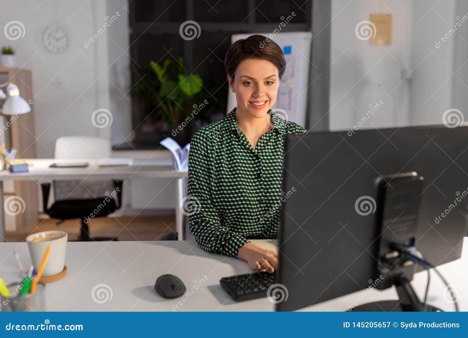 Bizneswoman pracuje na komputerze przy nocy biurem