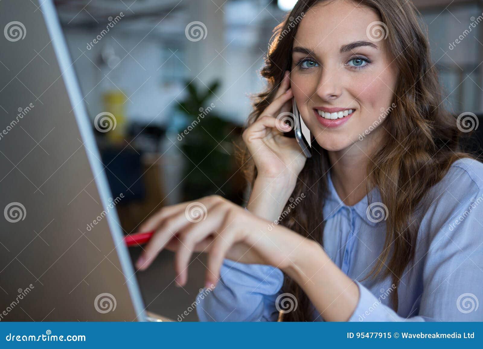Bizneswoman pracuje nad komputerem na telefonie komórkowym podczas gdy opowiadający przy biurkiem