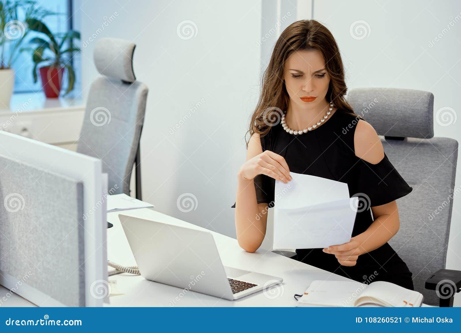 Bizneswoman siedzi przy biurkiem z komputerem i sprawdza dokumenty