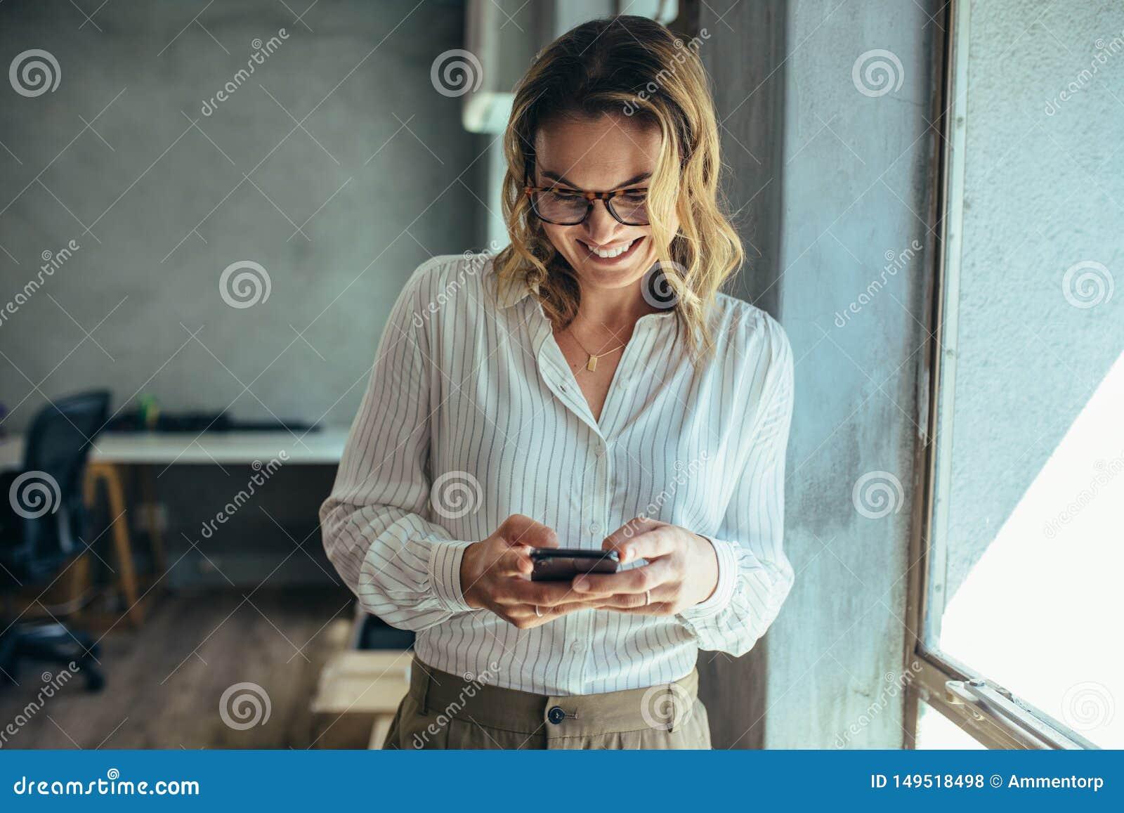 Bizneswoman u?ywa jej m?drze telefon w biurze