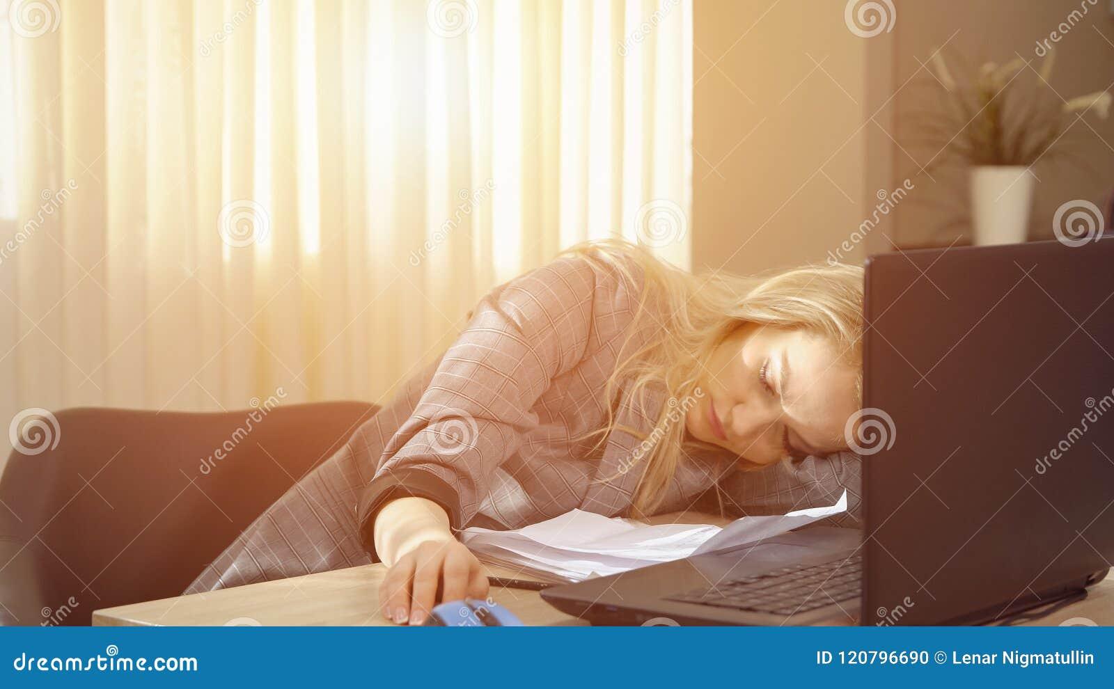 Bizneswoman w kostiumu ma drzemkę właśnie wyprostowywa na laptop klawiaturze po pracy