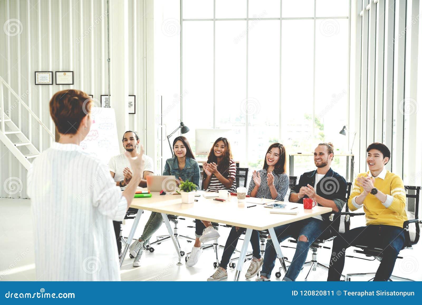 Bizneswoman wyjaśnia pomysły grupa kreatywnie różnorodna drużyna przy nowożytnym biurem Tylni widok gestykuluje rękę stoi znowu k