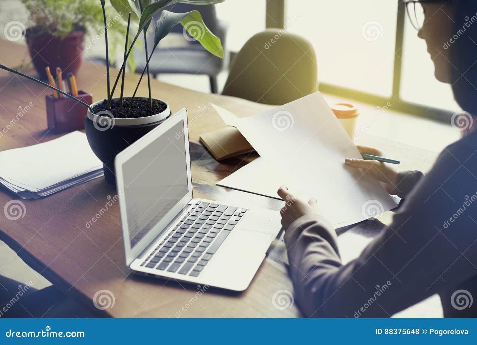 Bizneswoman z dokumentu papieru prześcieradłem w loft nowożytnym biurze, pracuje na laptopie Drużynowy działanie, ludzie biznesu