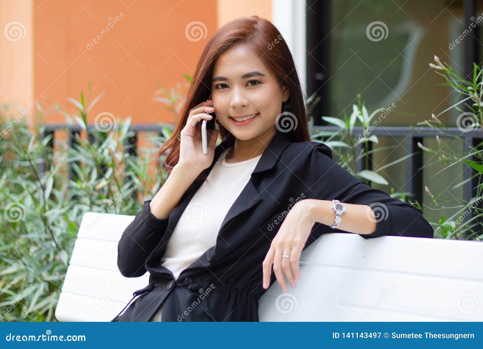 Bizneswomanu azjata używa telefon dla celling i texting na jej telefonie komórkowym