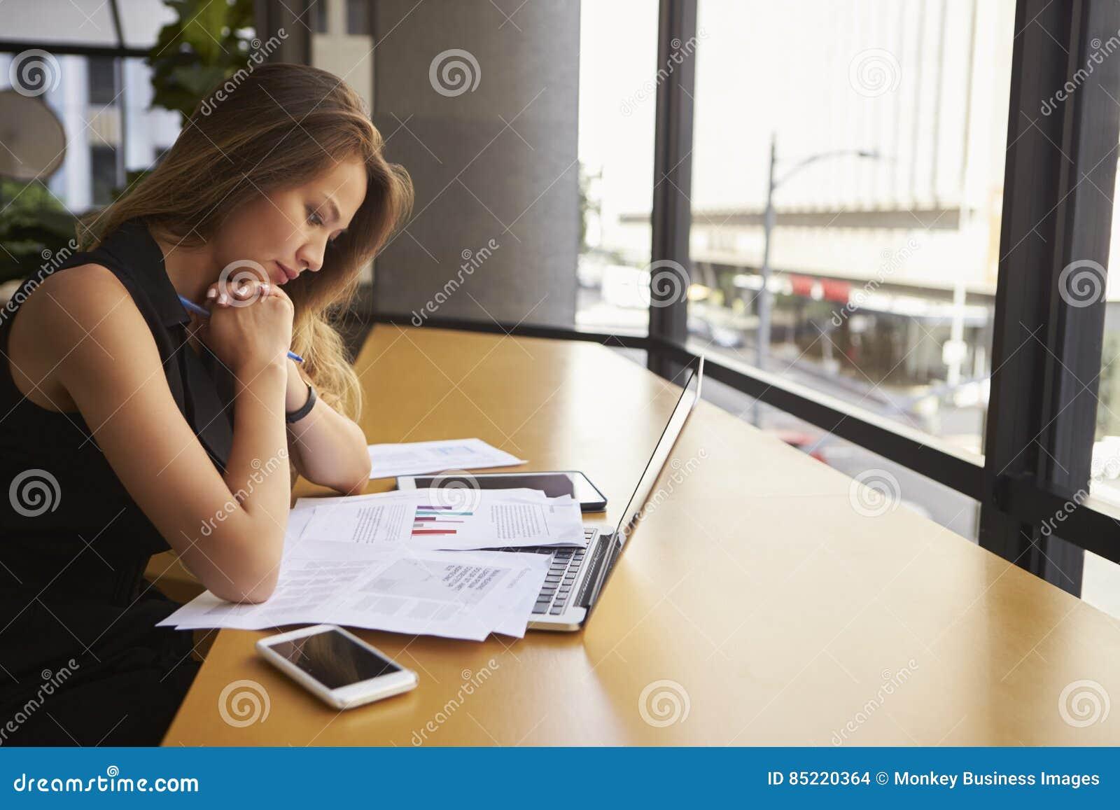 Bizneswomanu czytania pracujący dokument w biurze, boczny widok