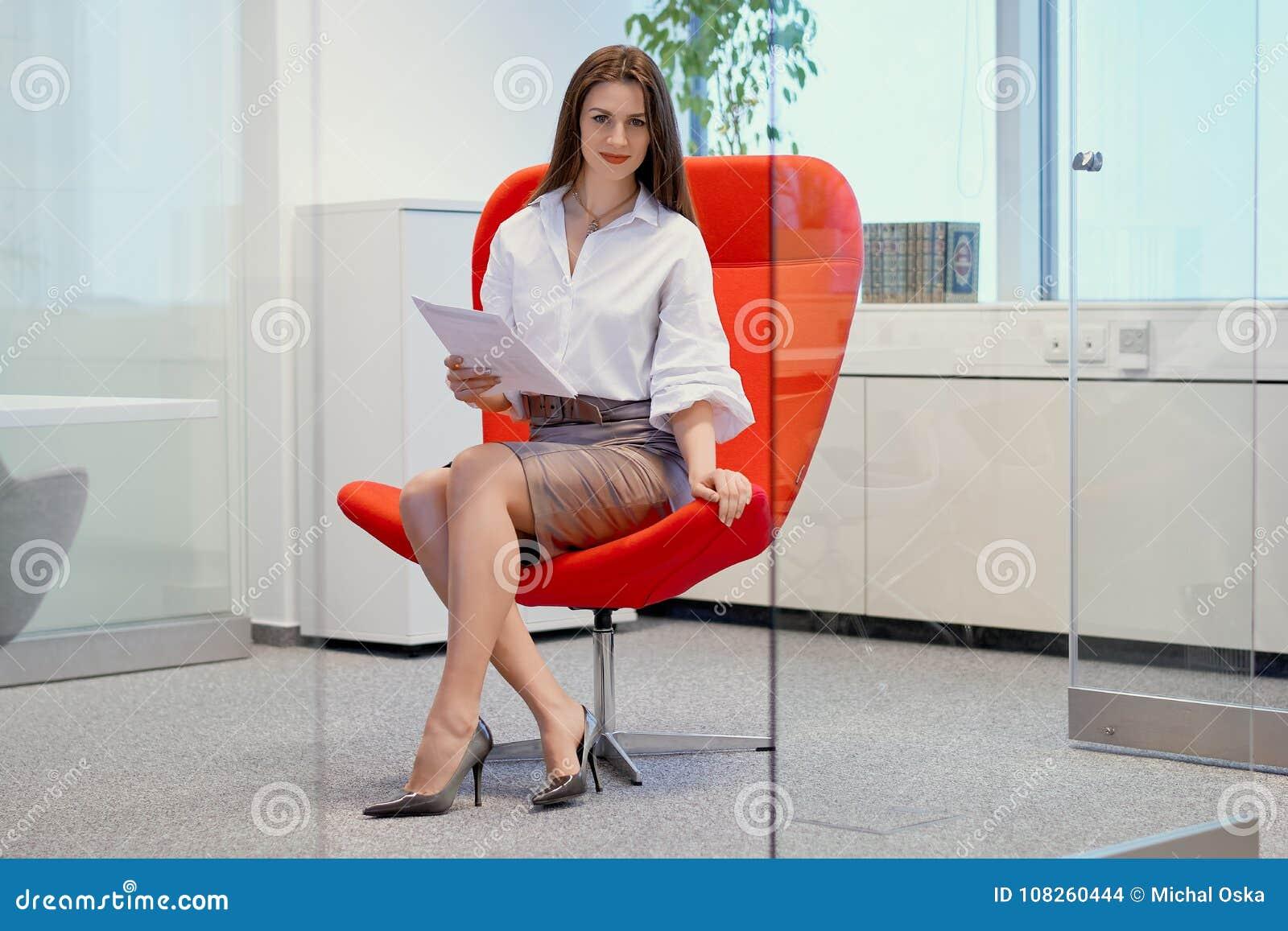 Bizneswomanu obsiadanie na czerwonym krześle w szklanym biurze i sprawdza dokumenty