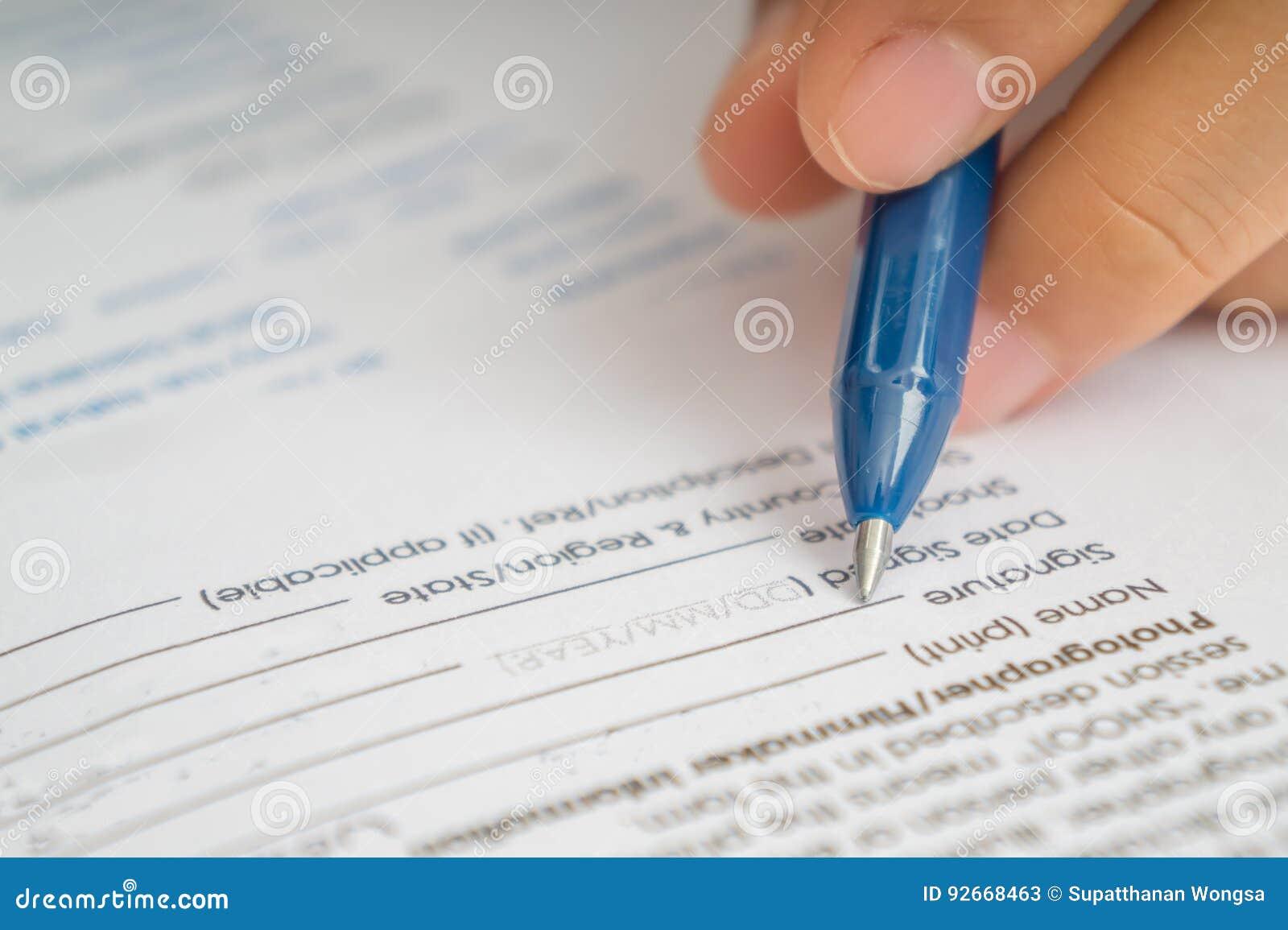Bizneswomanu podpisywania biznesowa kontraktacyjna zgoda, zamyka up żeńska ręka z ołówkowym writing podpisem