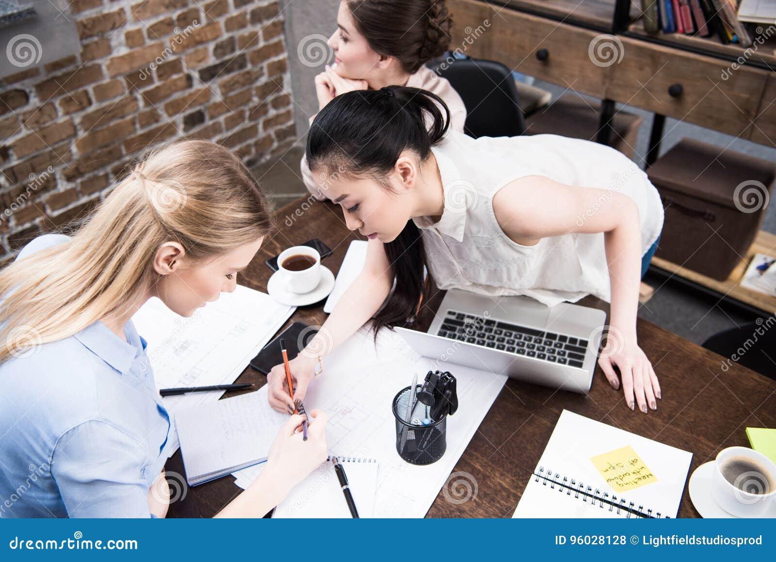 Bizneswomany dyskutuje projekt i pisze coś w notepad wpólnie przy workspace