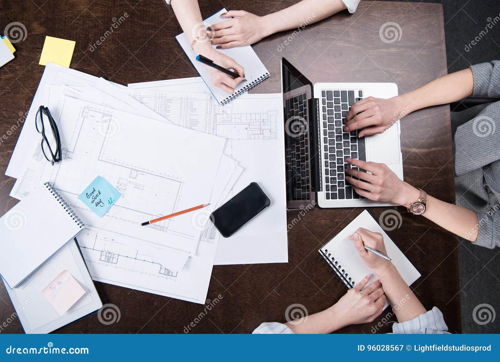 Bizneswomany pisze przy notatnikami i działaniem na laptopie