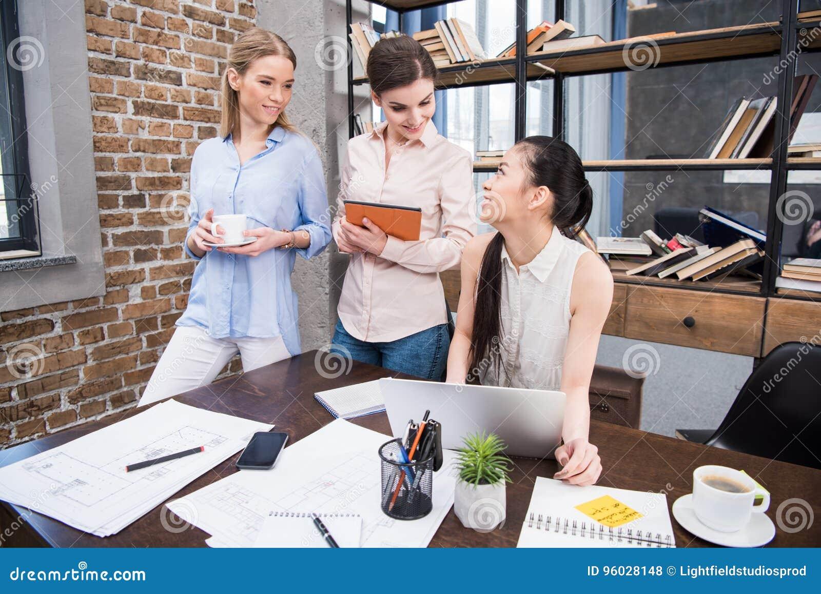 Bizneswomany pracuje z laptopem i cyfrową pastylką przy miejscem pracy w nowożytnym biurze