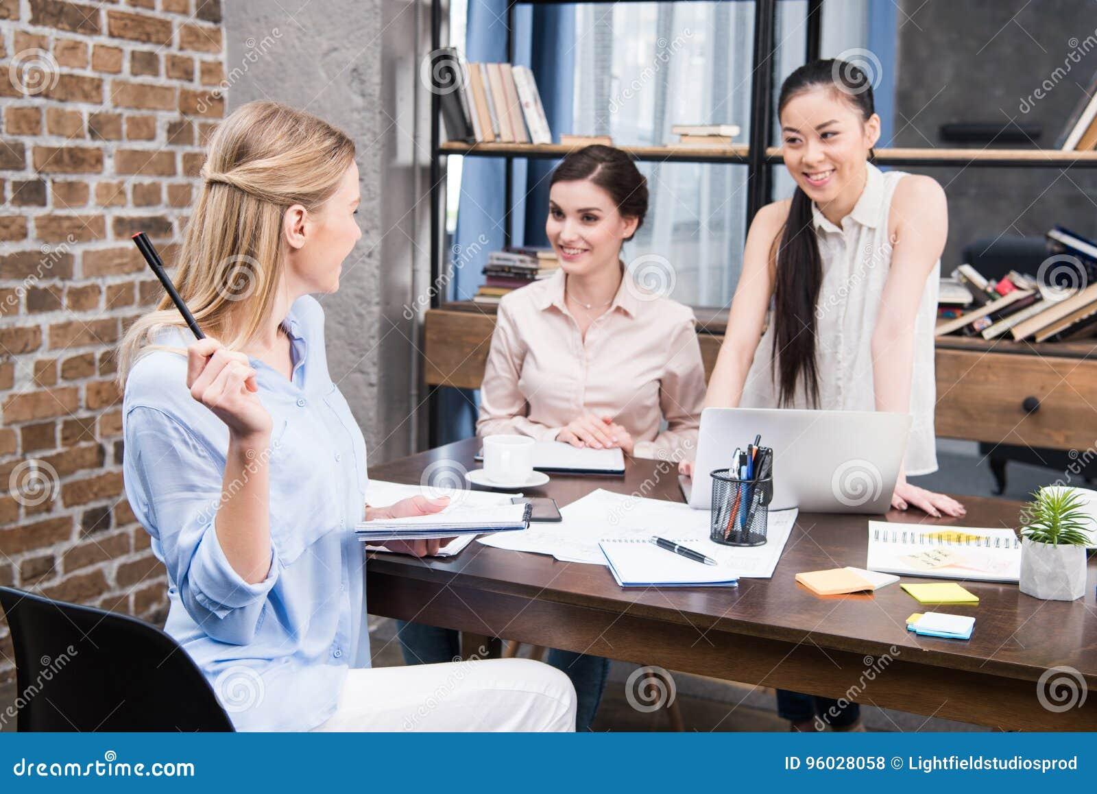 Bizneswomany pracuje z laptopem i dyskutuje projekt przy miejscem pracy w nowożytnym biurze