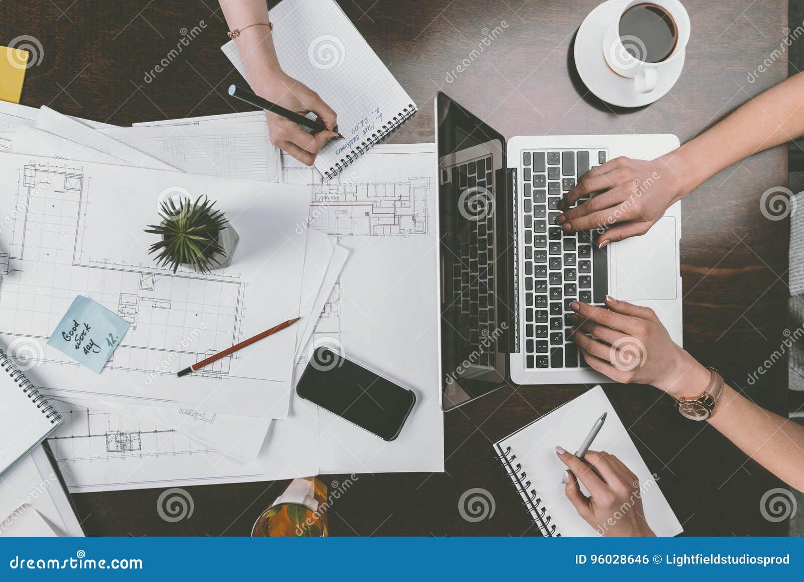 Bizneswomany pracuje z laptopem i notepads na drewnianym tabletop przy workspace