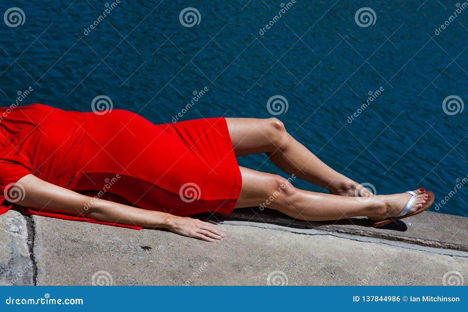 Blähen dünne zierliche schwangere Damen auf An sich hinlegen im roten Kleid