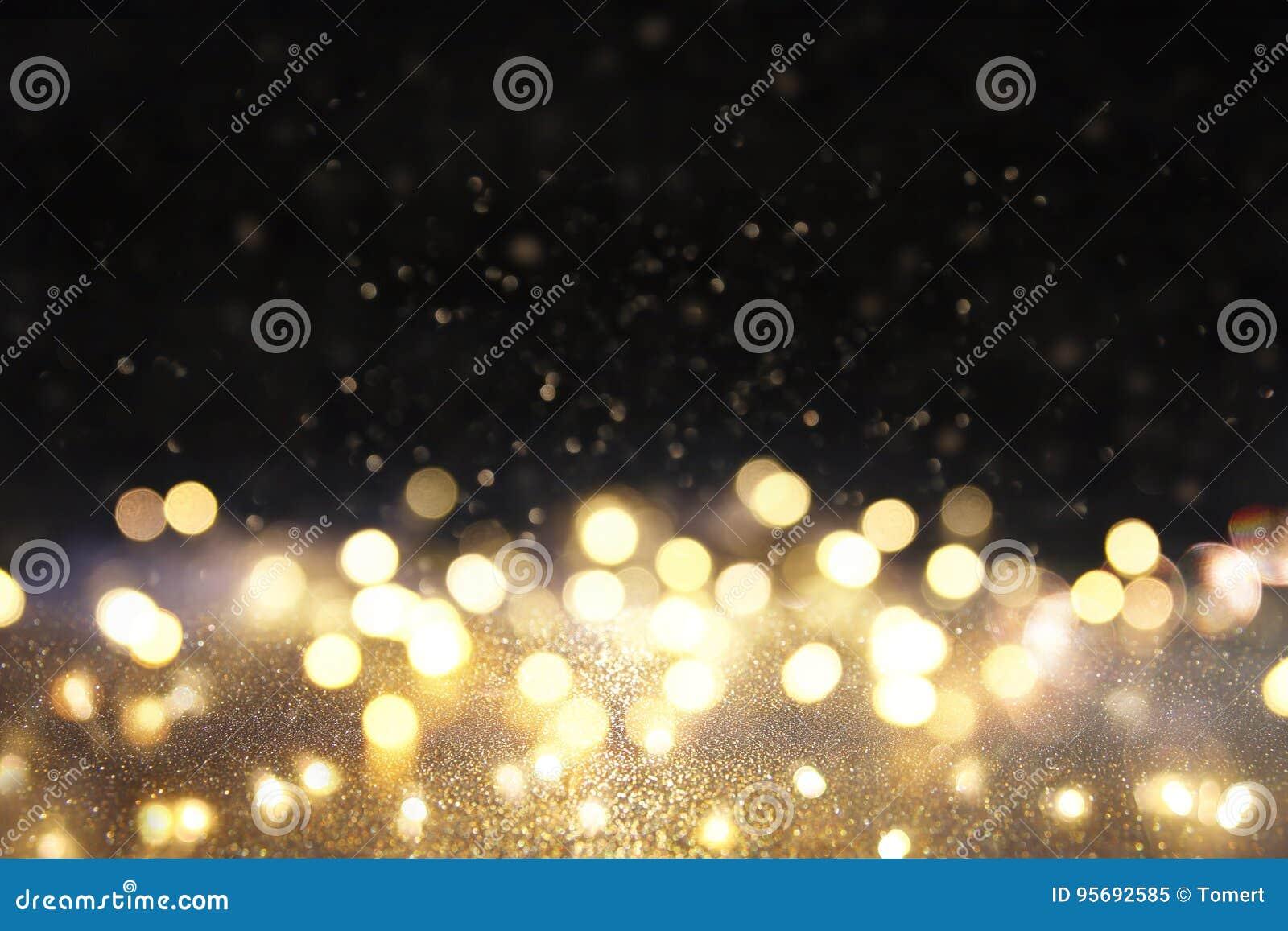 Blänka tappningljusbakgrund svart guld defocused