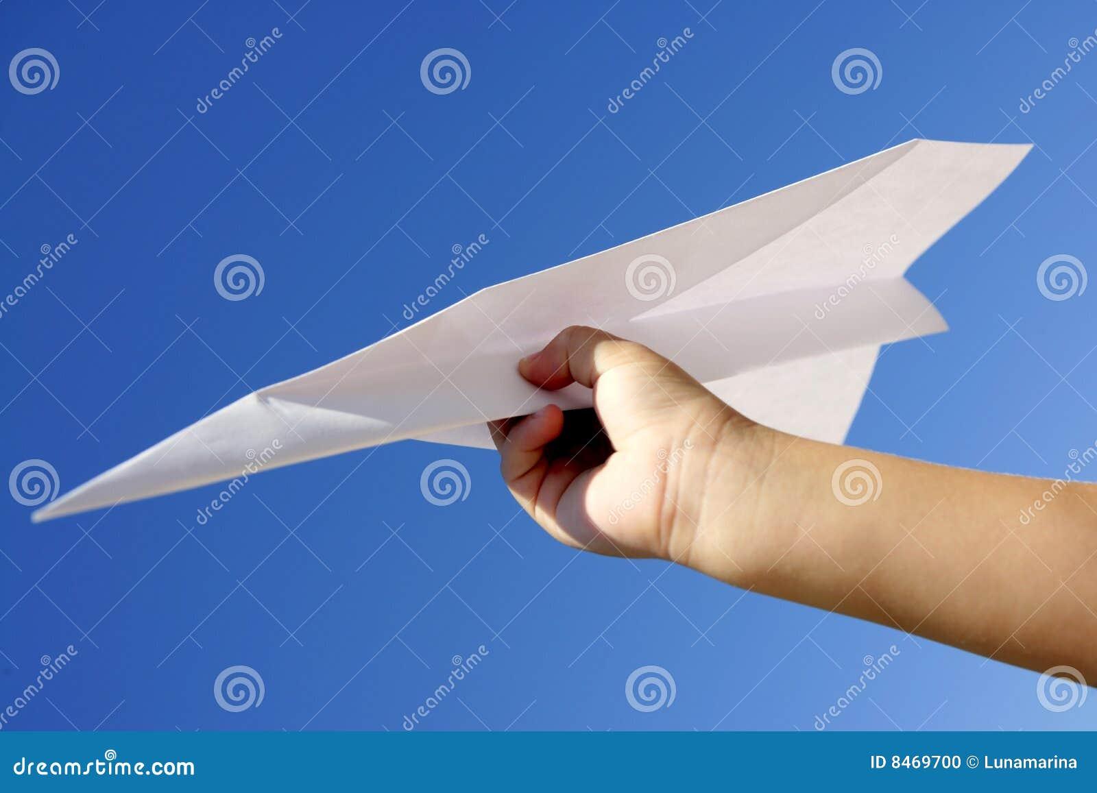 Blå barnhand för flygplan över den paper skyen