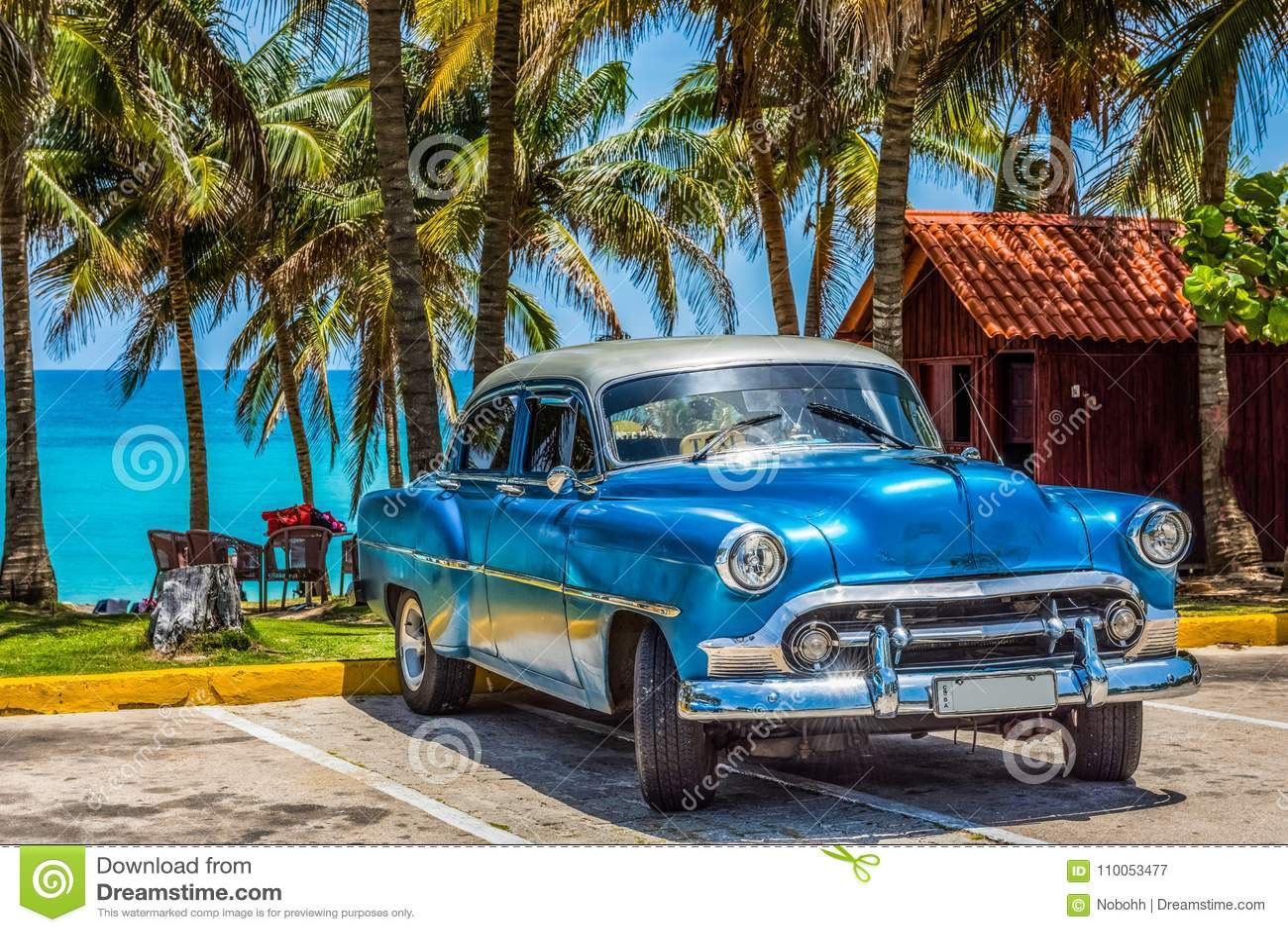 Blå Chevrolet för amerikan klassisk bil med silvertaket som parkeras på stranden i den Varadero Kuban - Serie Kubareportage