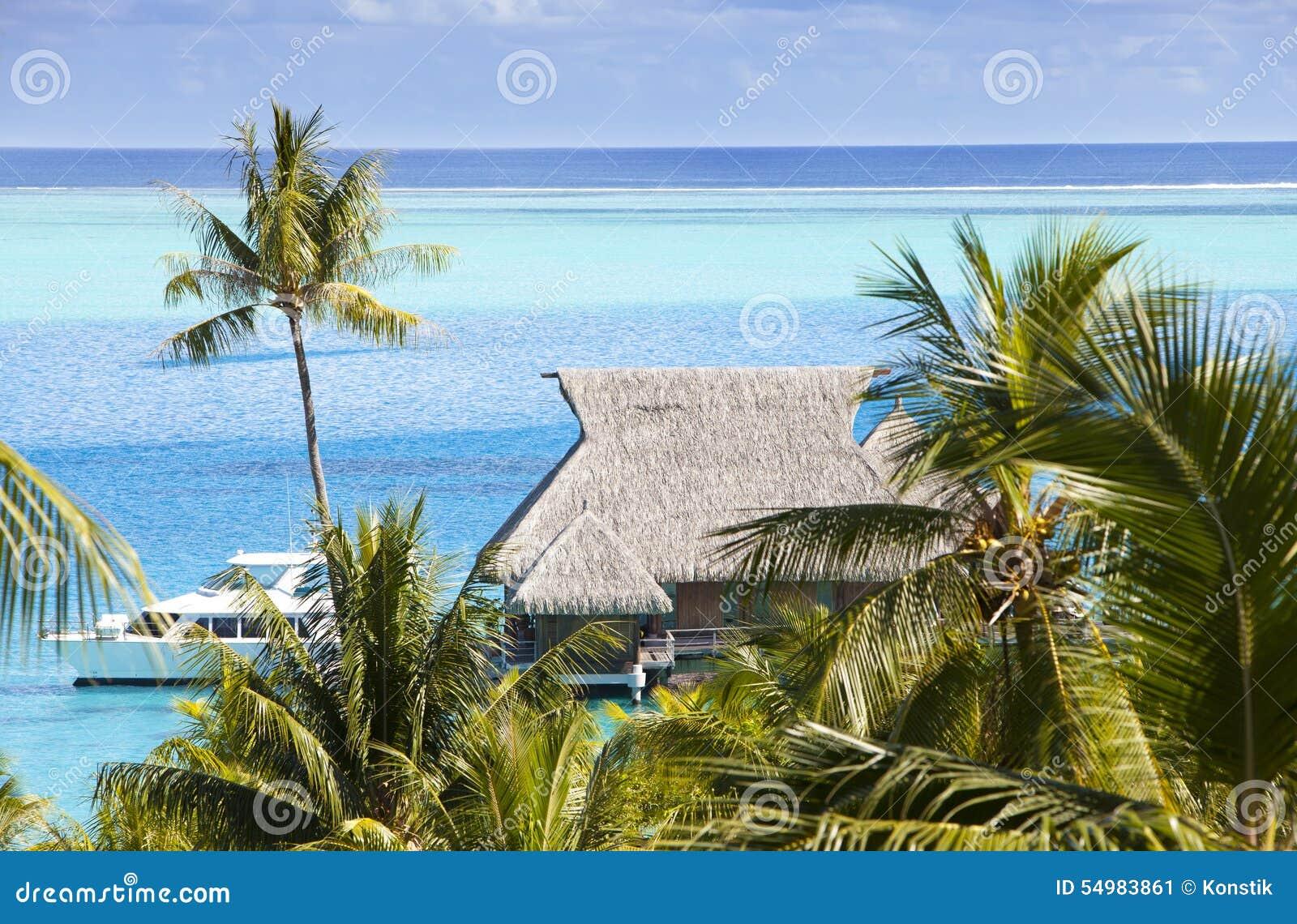 Blå lagun av ön av Bora Bora, Polynesien En sikt från höjd på palmträd, traditionella logar över vatten och havet
