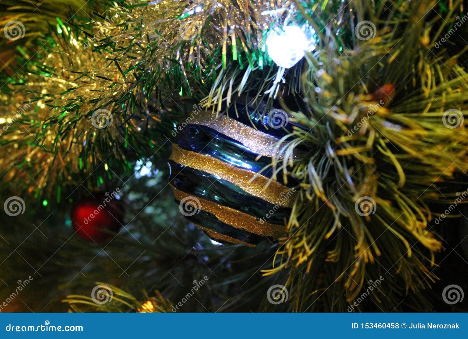 Blå prydnad som hänger på en julgran