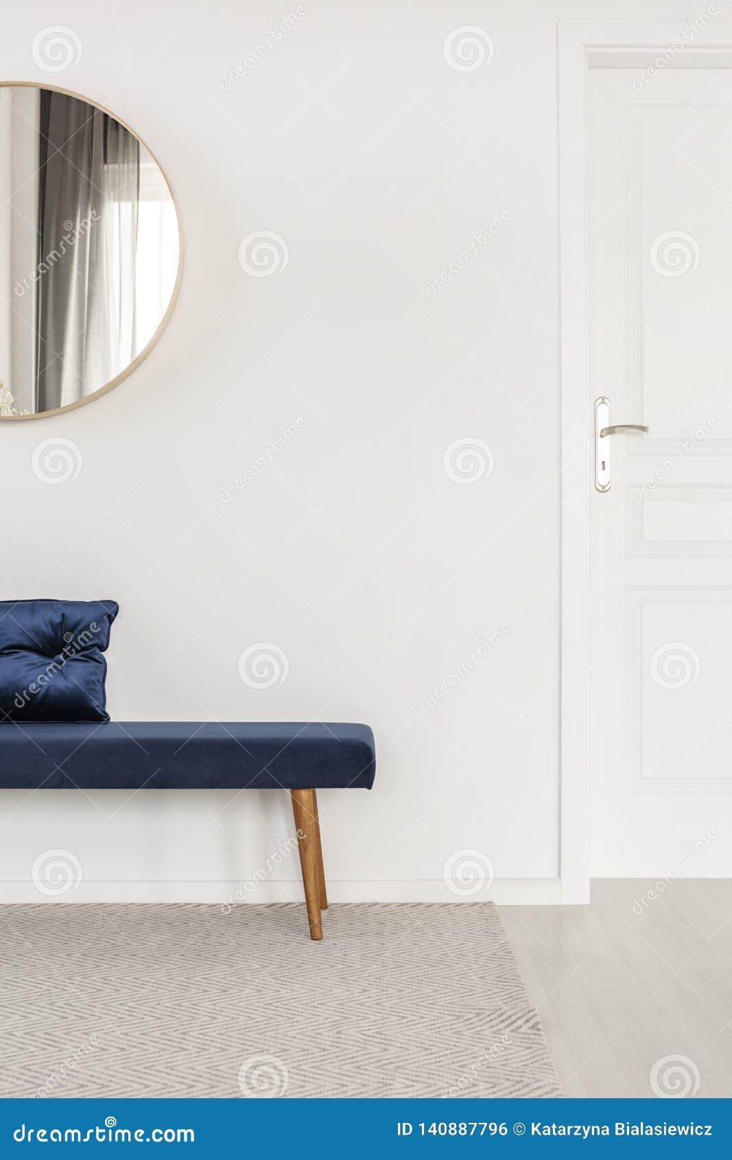 Blå sammetbänk med kudden i den vita och ljusa korridoren