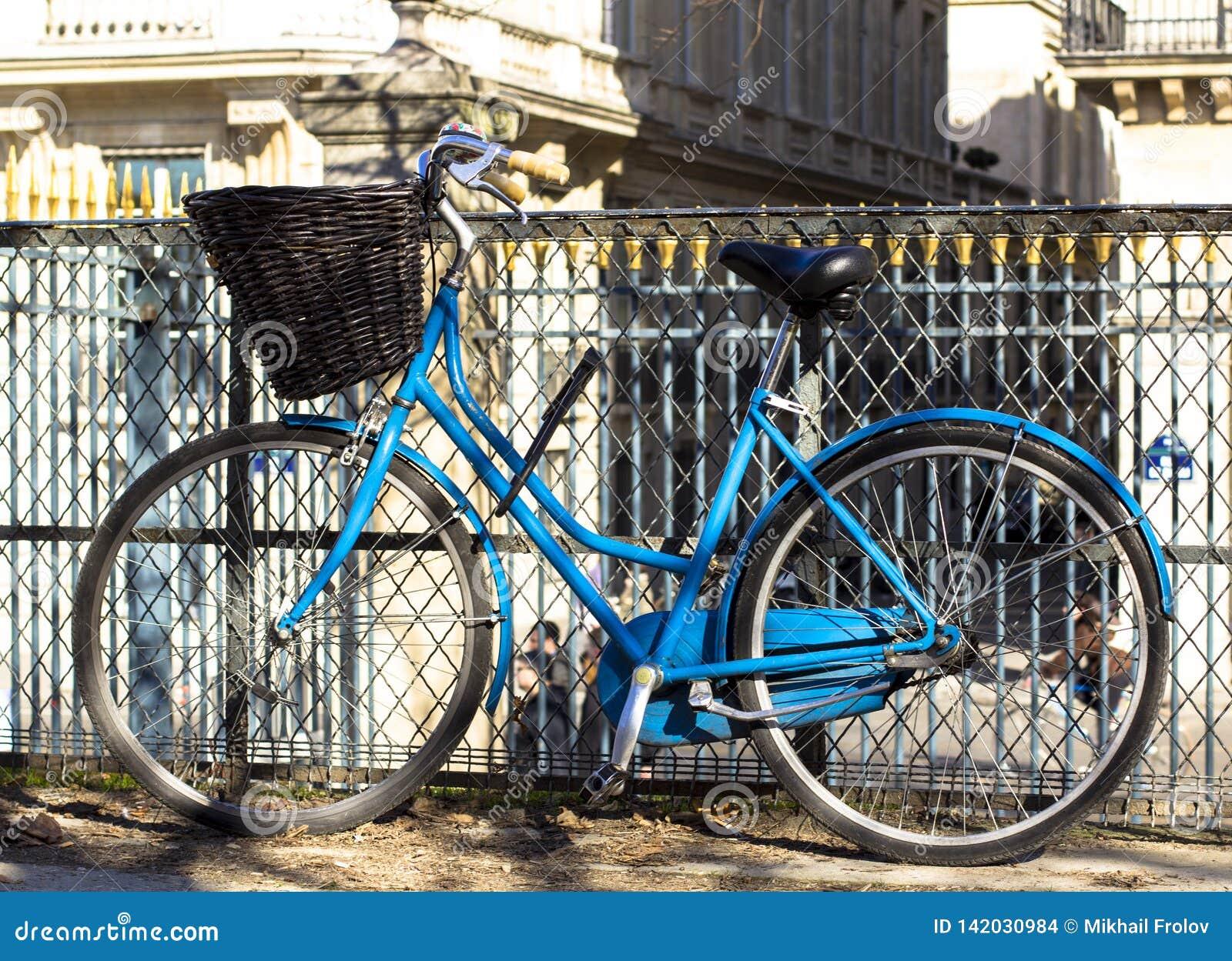 Blå tappningcykel med korgen på staketet