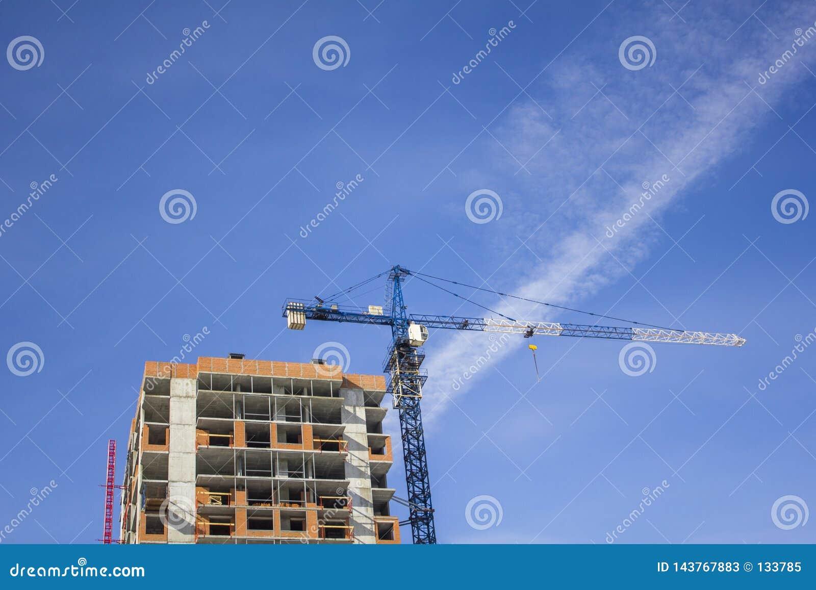 Blå tornkran nära en högväxt byggnad under konstruktion på bakgrunden av en klar himmel