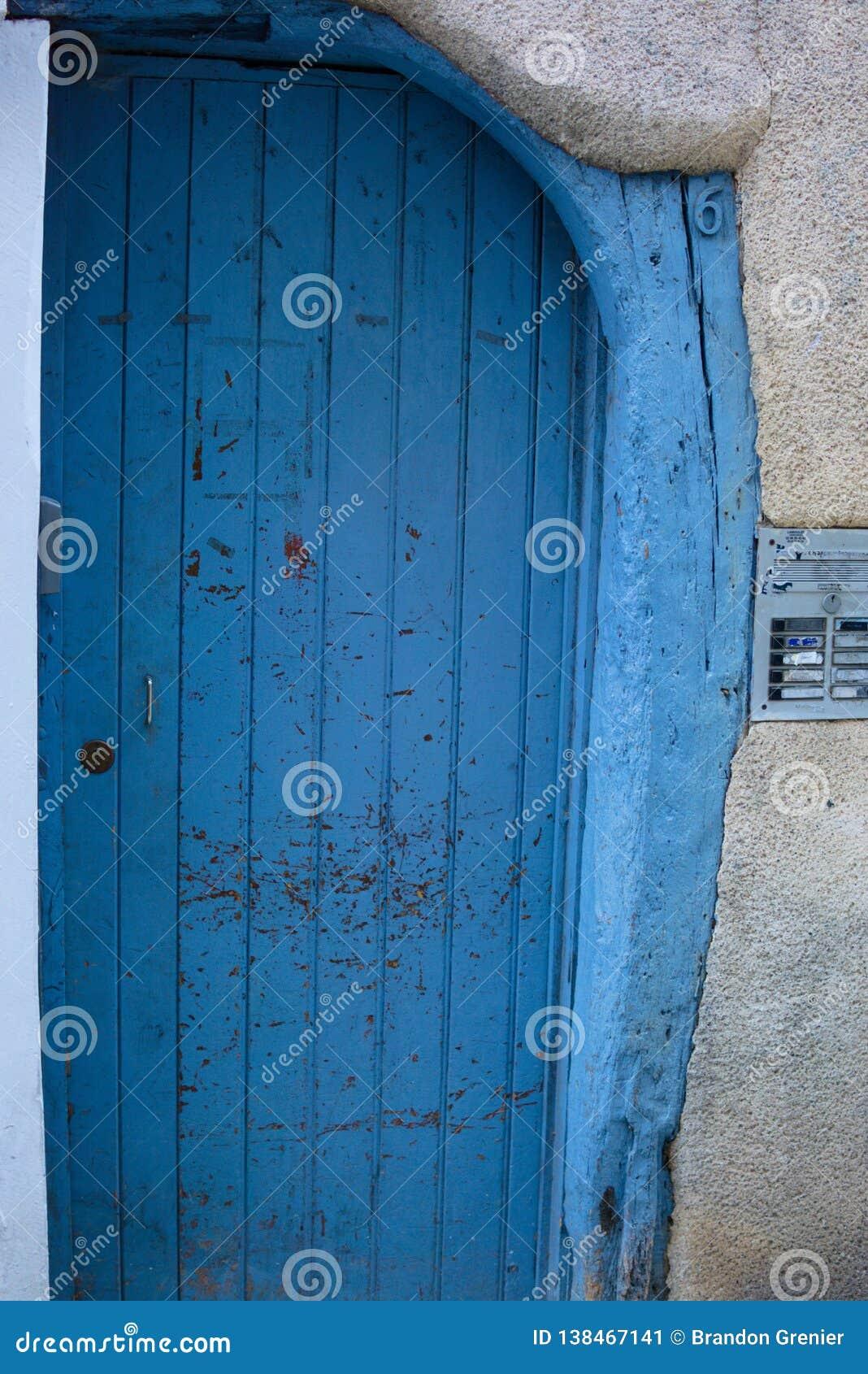 Blå trädörr med den yttre ingången för sten