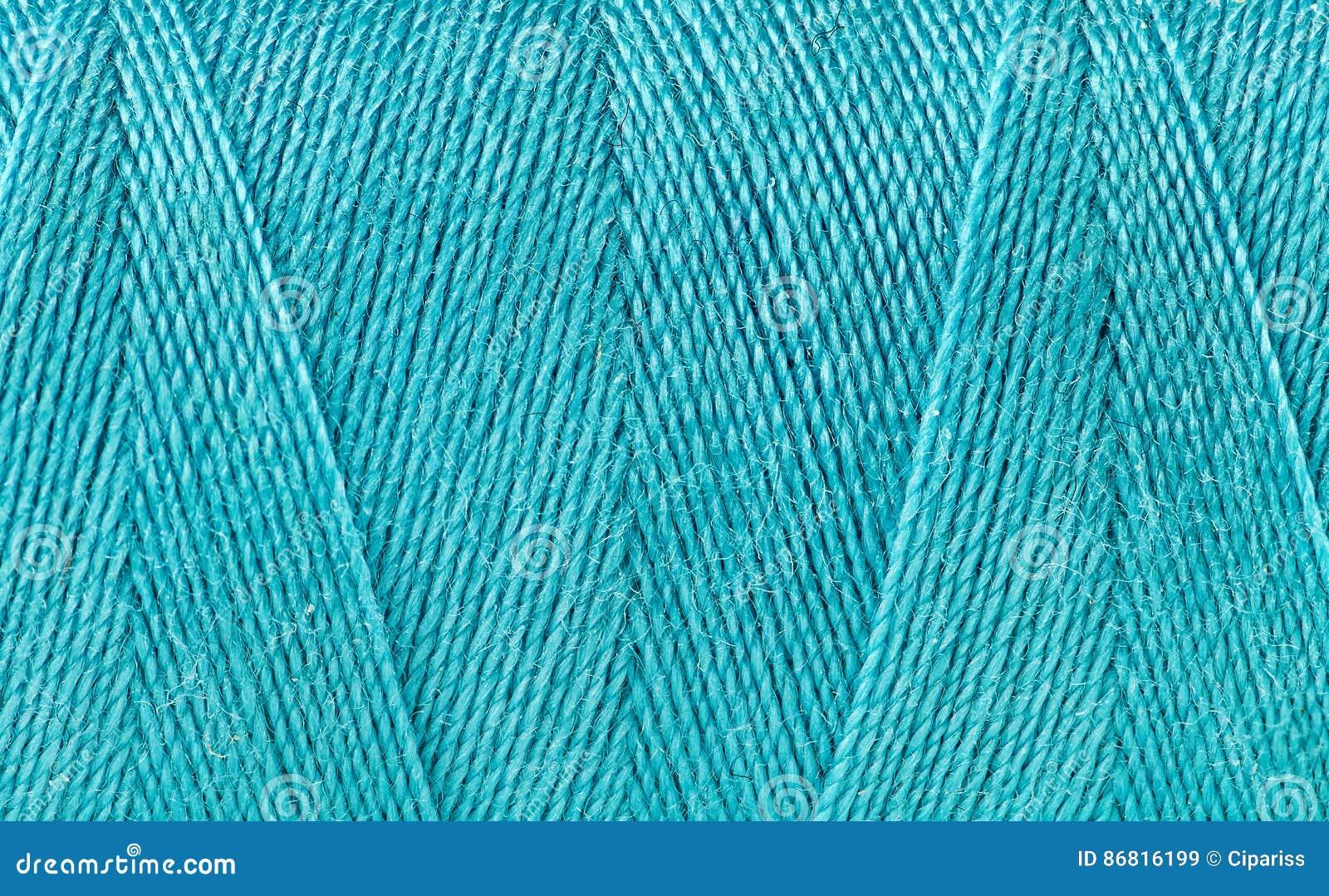Blå tråd som köas på en spole