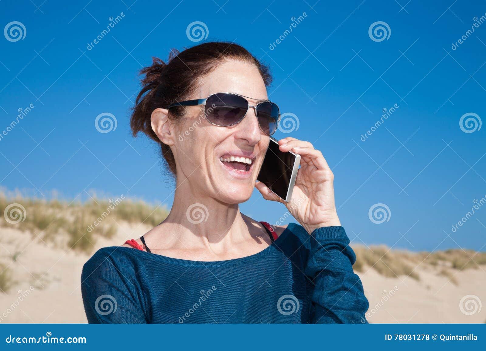 Blå tröjakvinna med solglasögon som talar på mobil