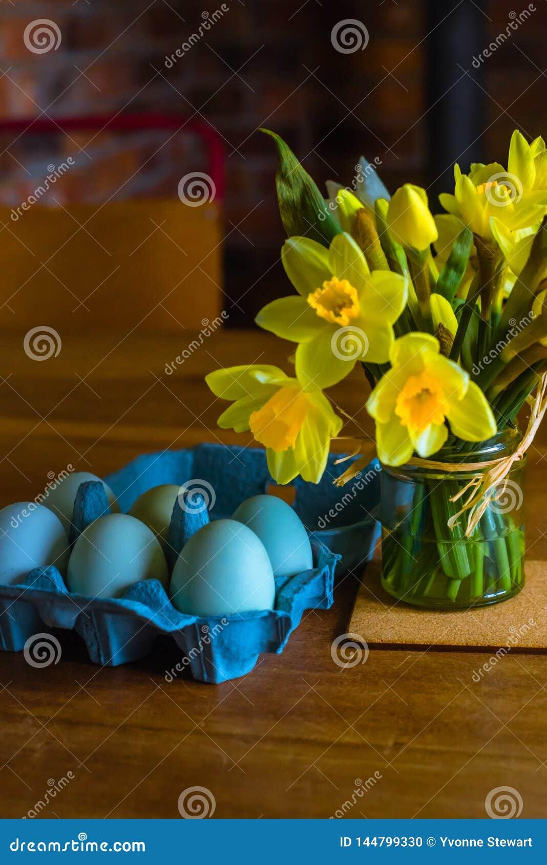 Blåa ägg och gula påskliljor på ett köksbord