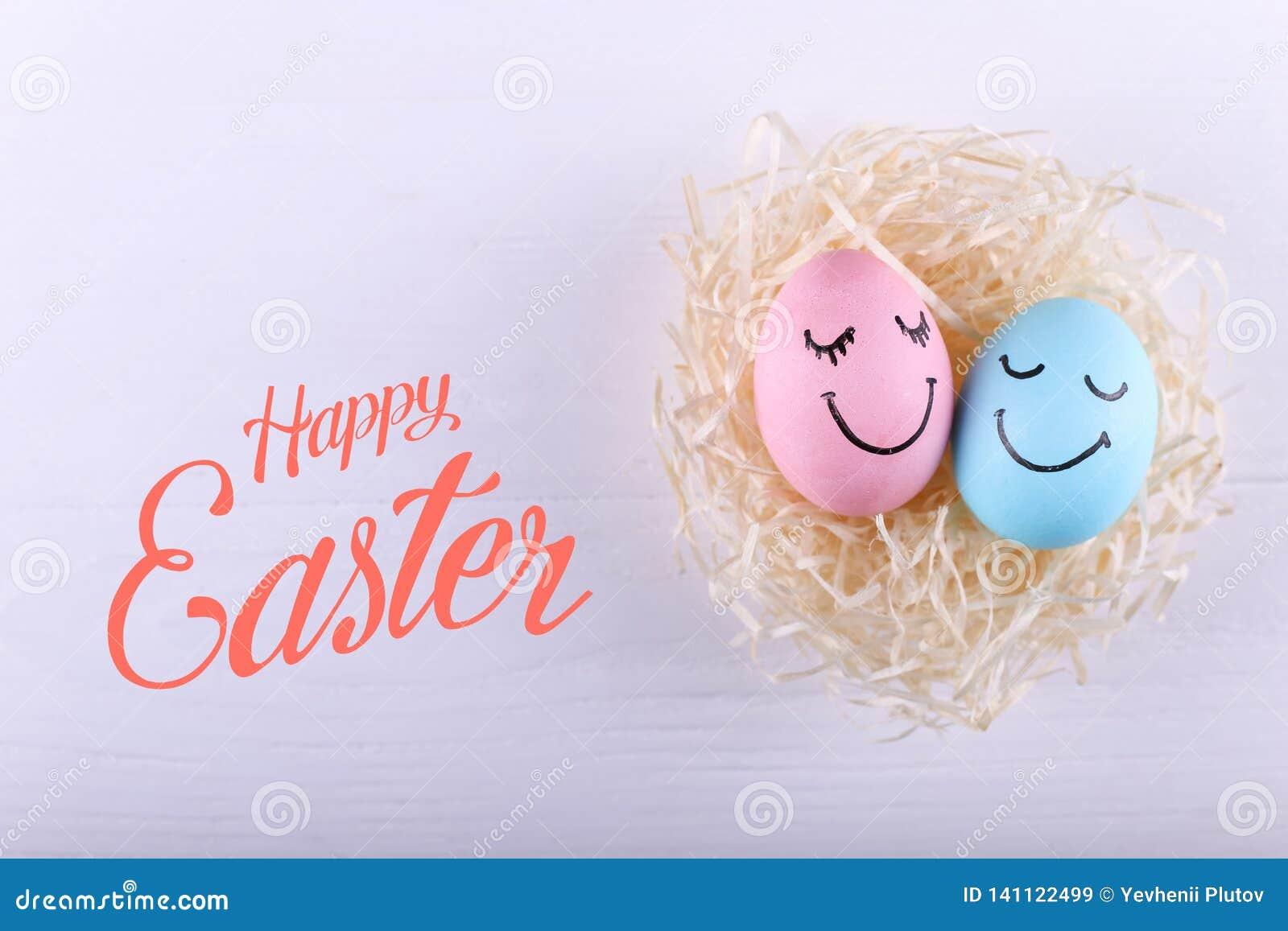 Blåa och rosa ägg med målade leenden i redet, kopieringsutrymme Lycklig design för kort för påskbegreppshälsning