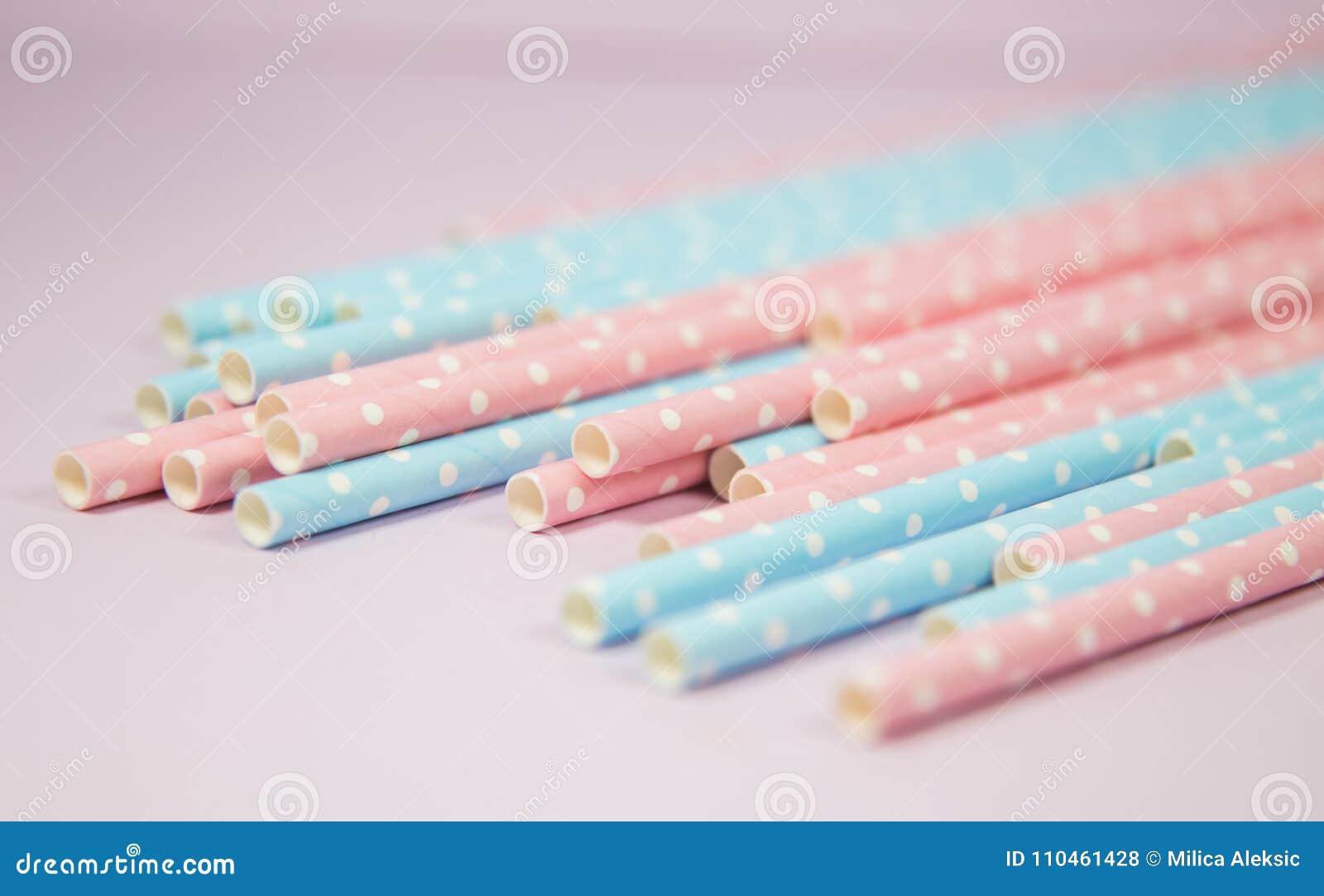 Blåa och rosa pricksugrör i den rosa bakgrunden