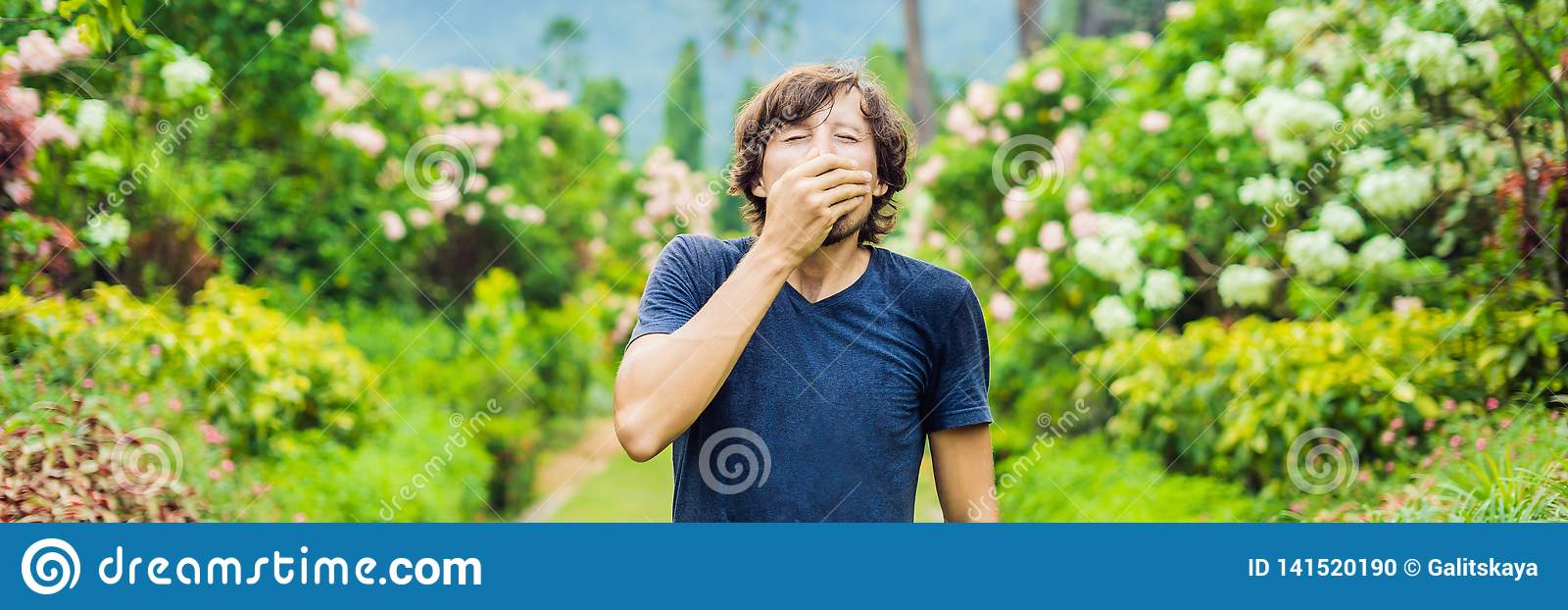 Blåsa näsa för ung man framme av att blomma trädet BANER för vårallergibegrepp, LÅNGT FORMAT