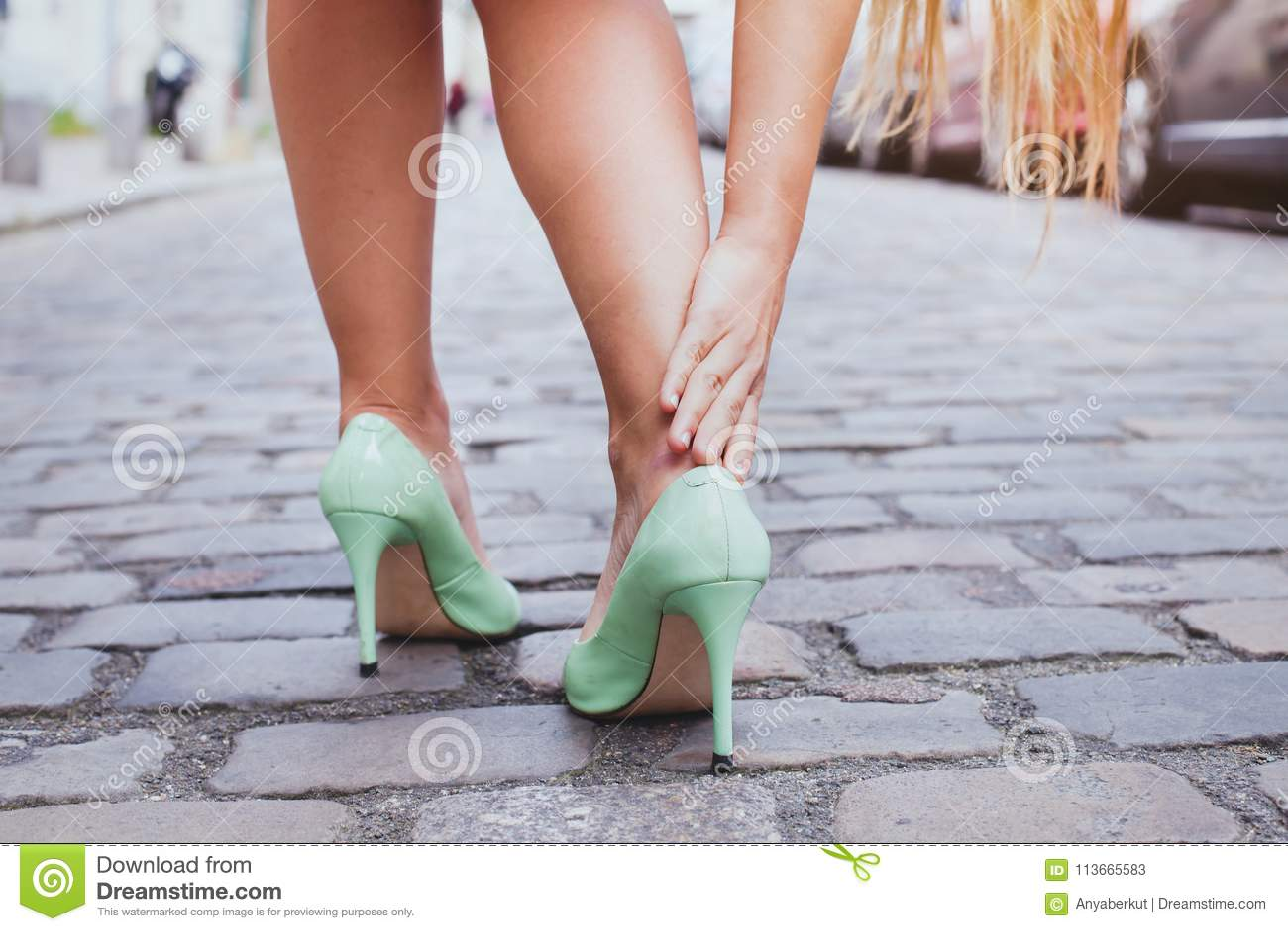 Blåsor kvinna på höga häl har smärtsamma skor