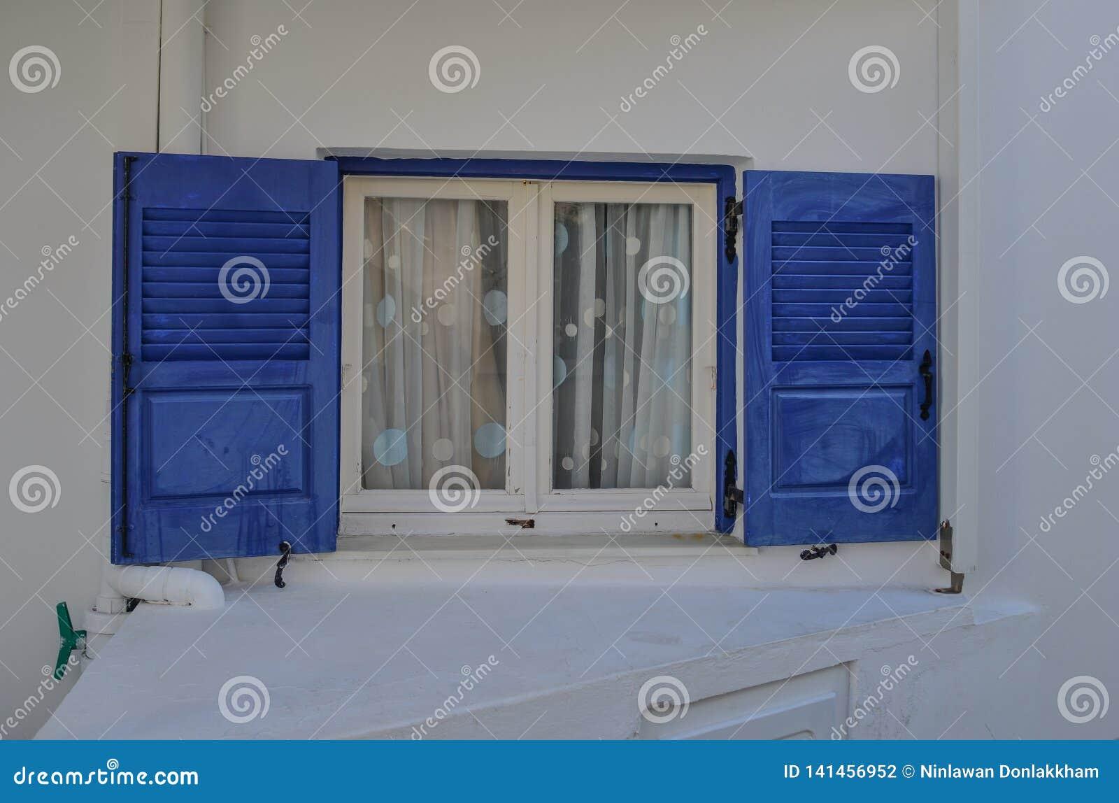 Blått fönster på typisk hus i Grekland