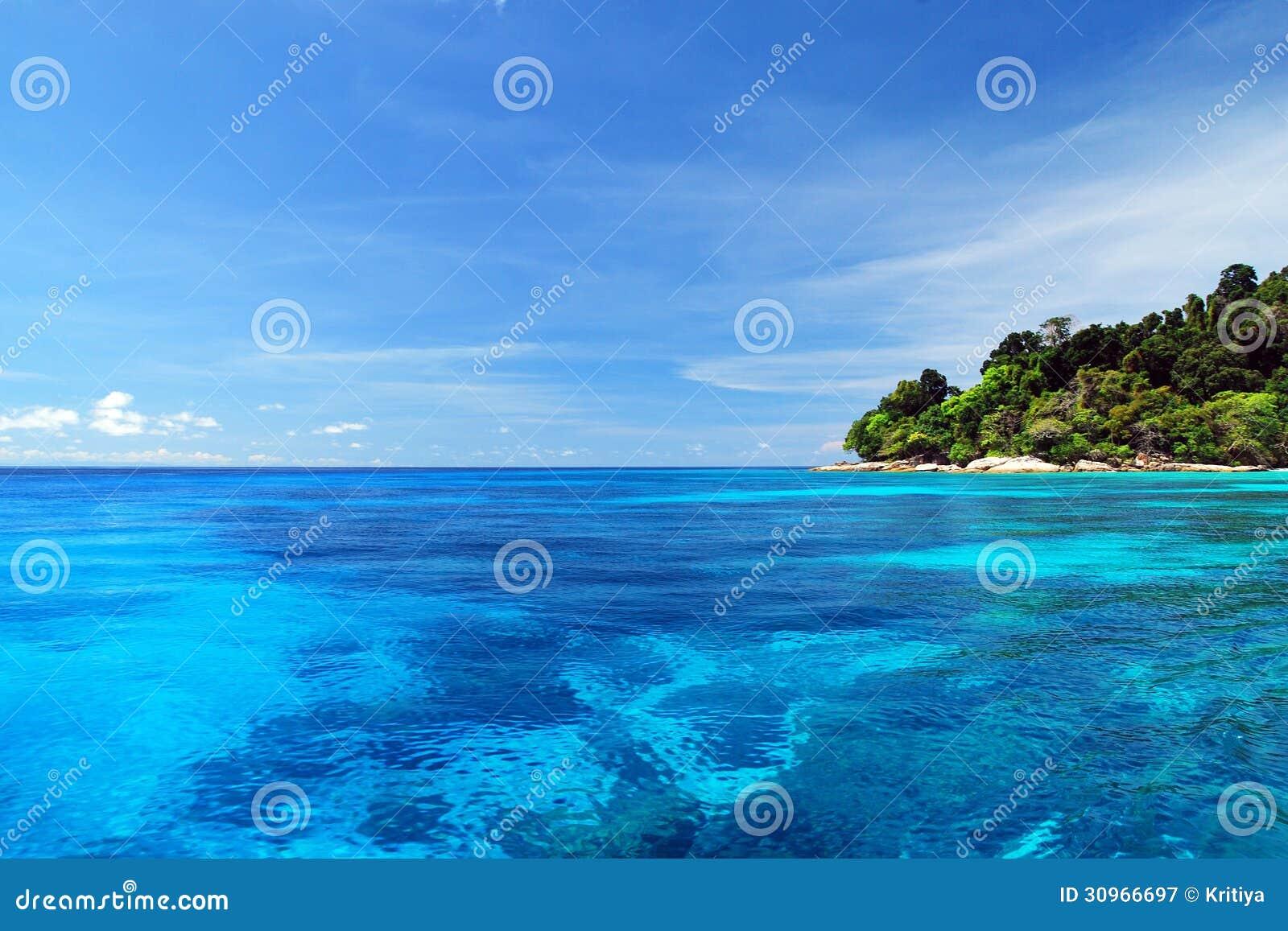 Blått hav med korallreven och fluffiga moln från tachaiön