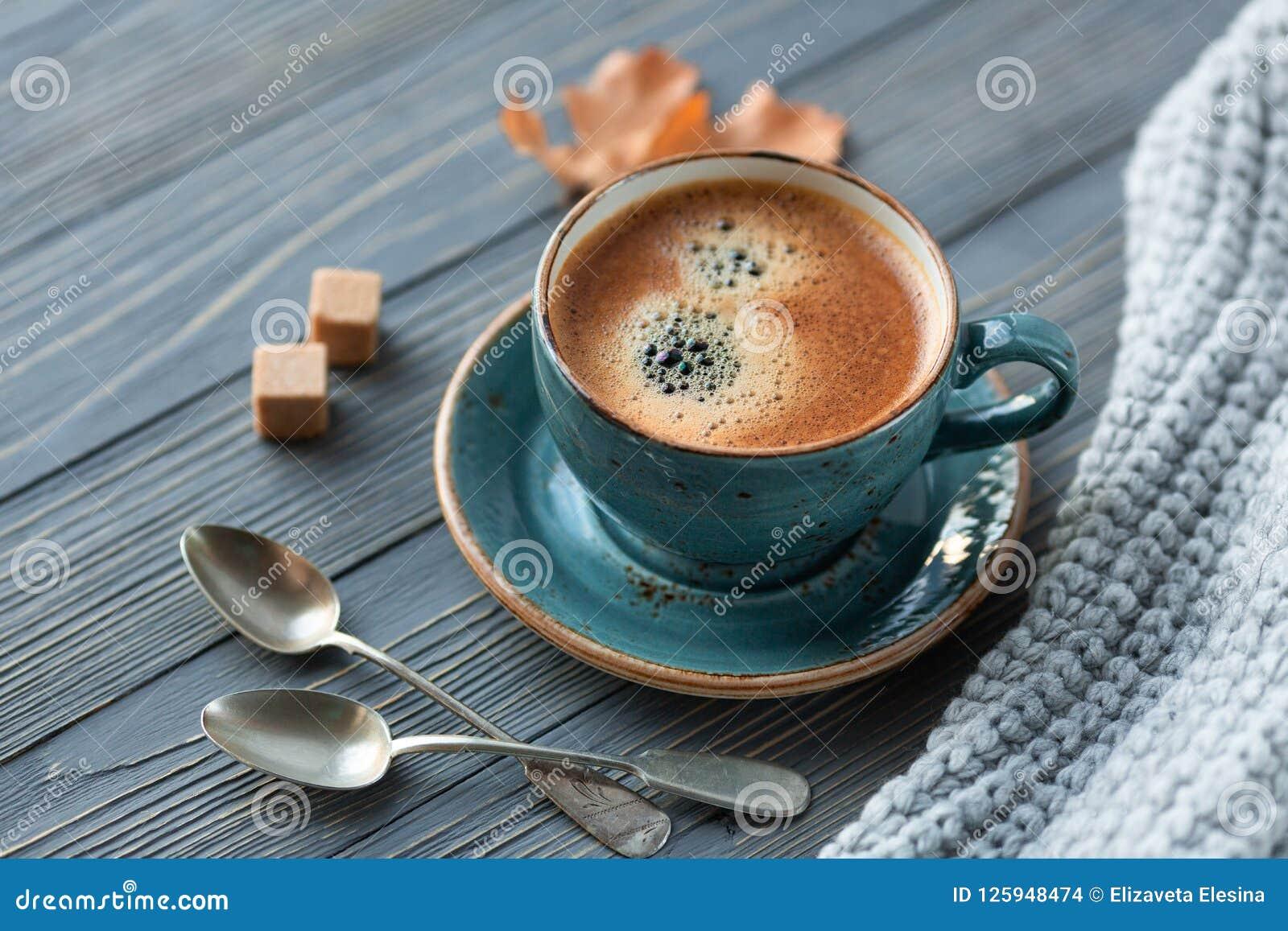 Blått koppwhithkaffe, stucken tröja, höstsidor på träbakgrund
