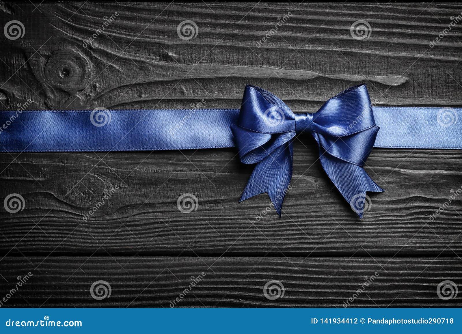 Blått pilbåge och band för gåva på en svart träbakgrund