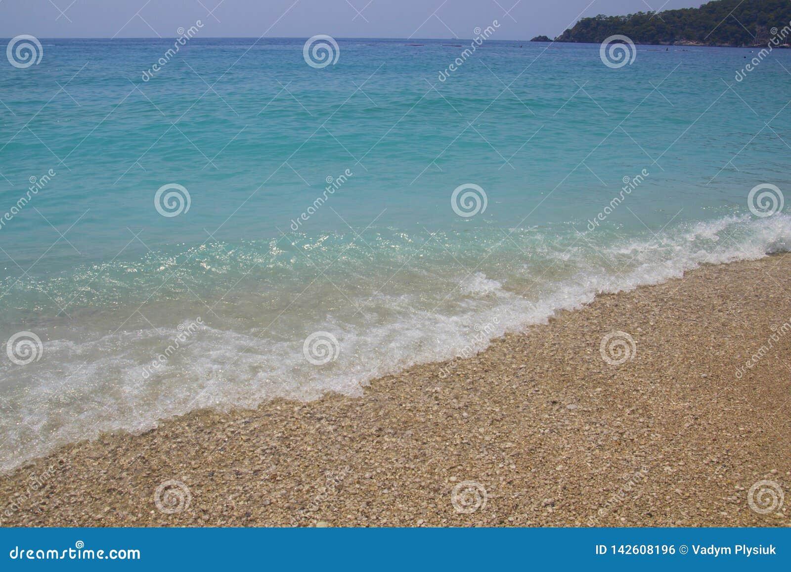 Blått vatten med havsskum Små vågor kommer till kusten Turkosvatten med vita kiselstenar på stranden Havslinjen möter