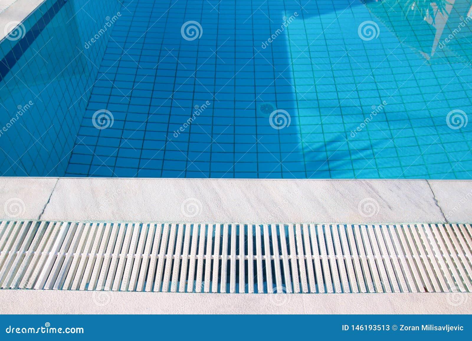 Bl?tt rivit s?nder vatten i simbass?ng i tropisk semesterort med kanten av trottoar Del av simbass?ngbottenbakgrund
